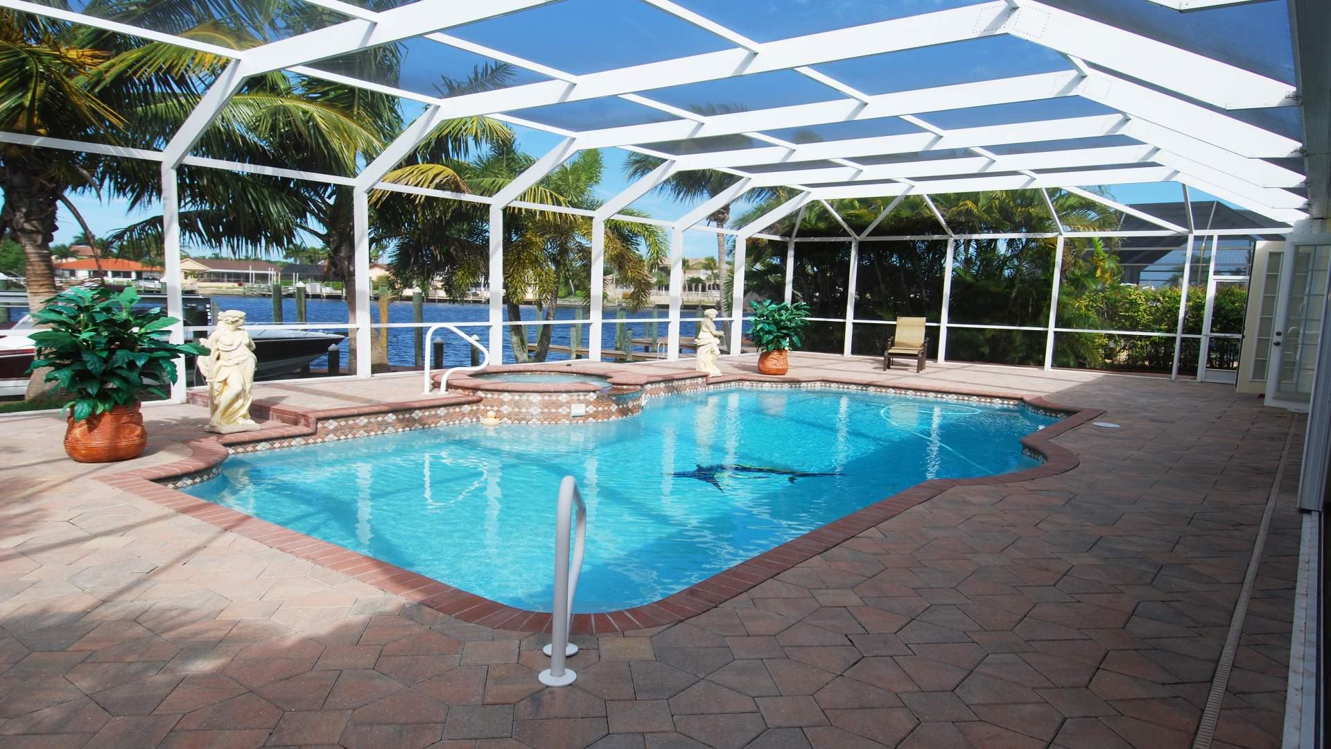 The paved pool area faces west and overlooks a wide sailboat canal