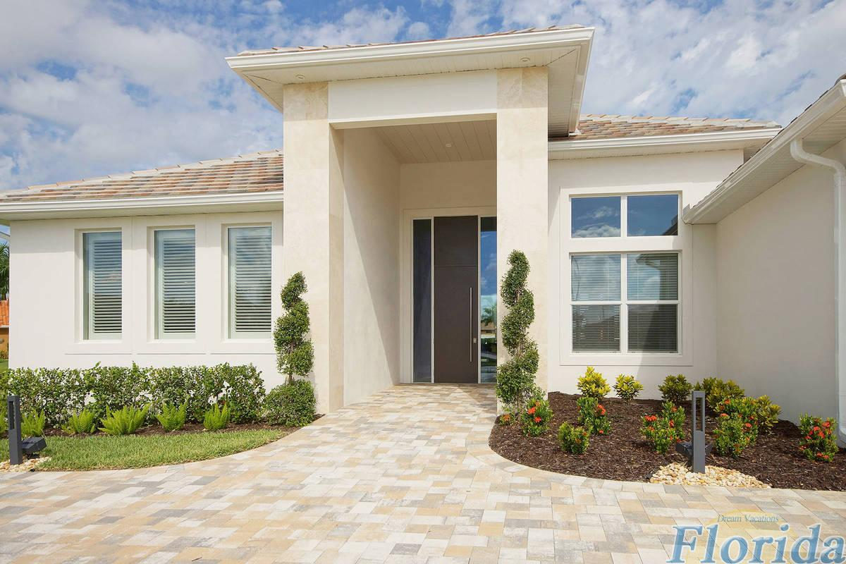 The entry impresses with clean lines and a paved driveway