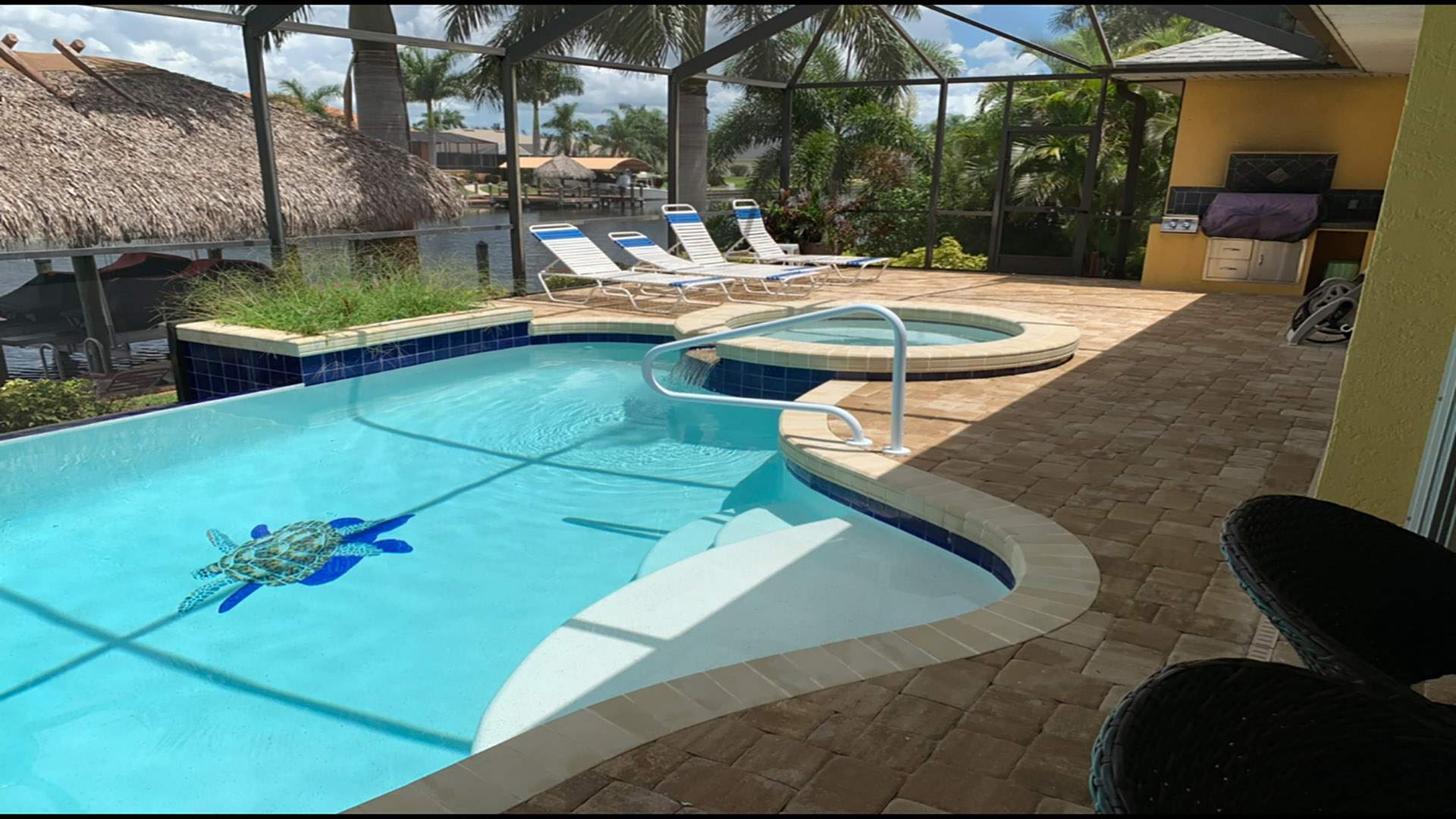 The inviting paved pool area includes a pool with vanishing edge effect